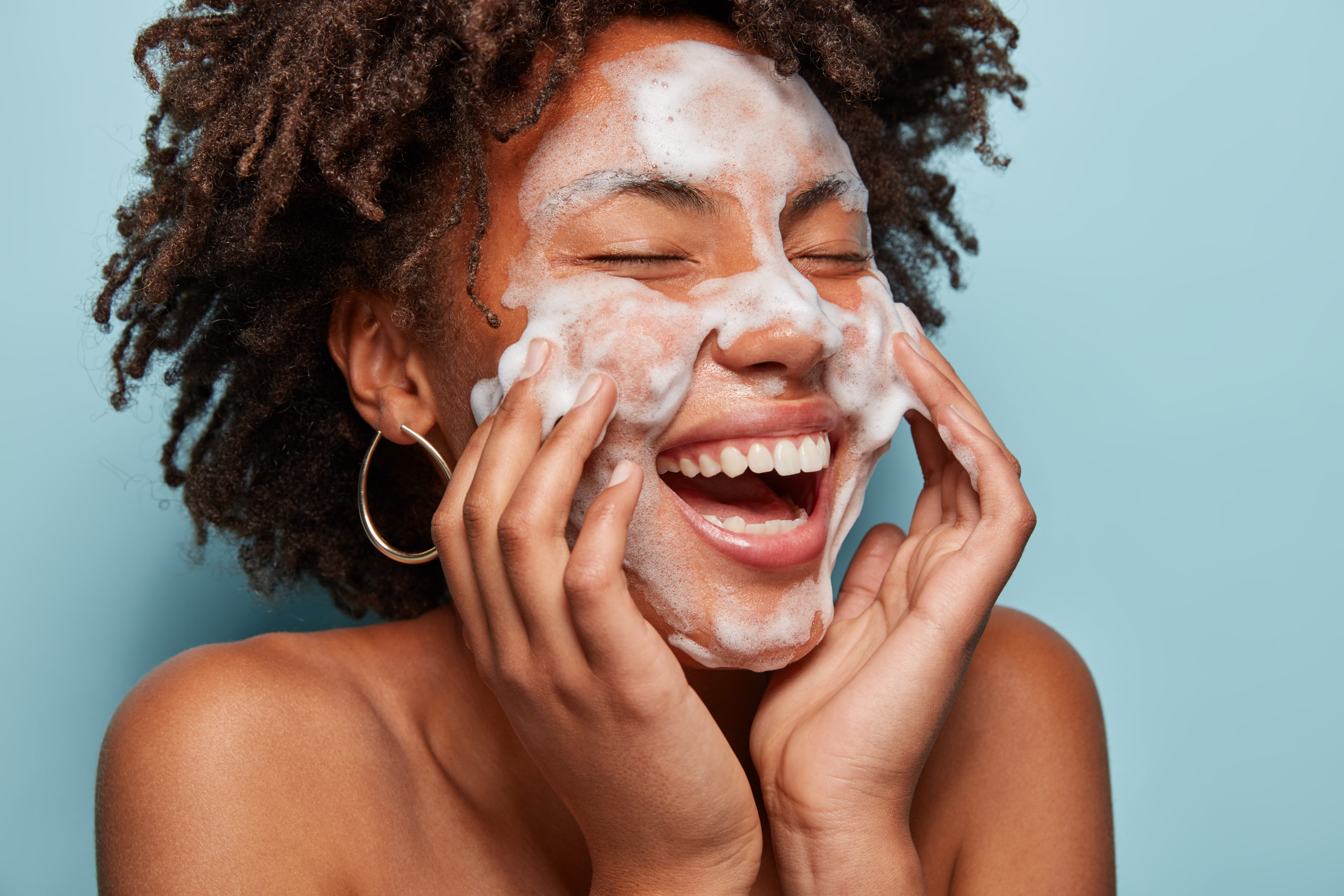 Cheerful woman washing her face and smiling